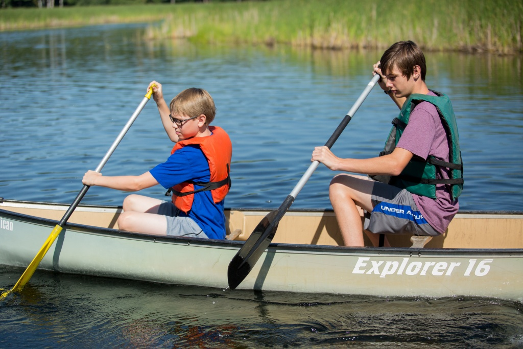Two kids paddling in a canoe.