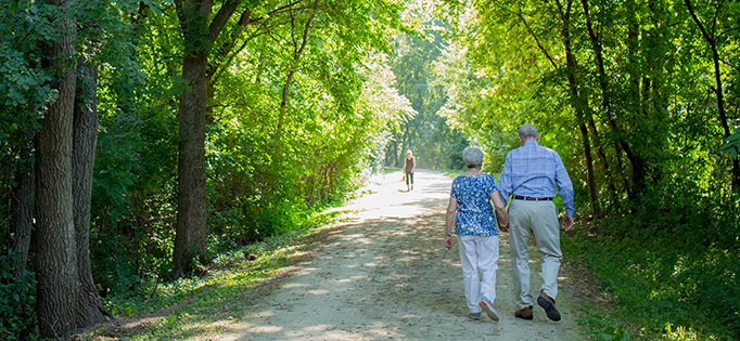 Older couple walking down a trail.