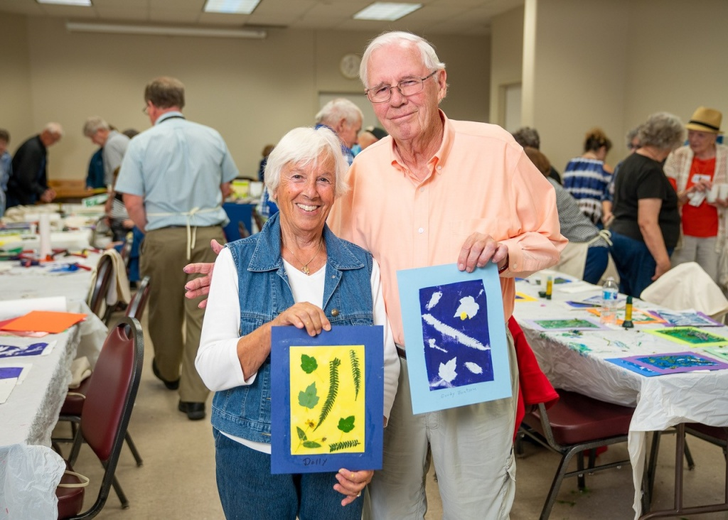 Older couple holding up their artwork.