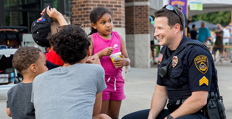 Police officer talking to children while smiling.